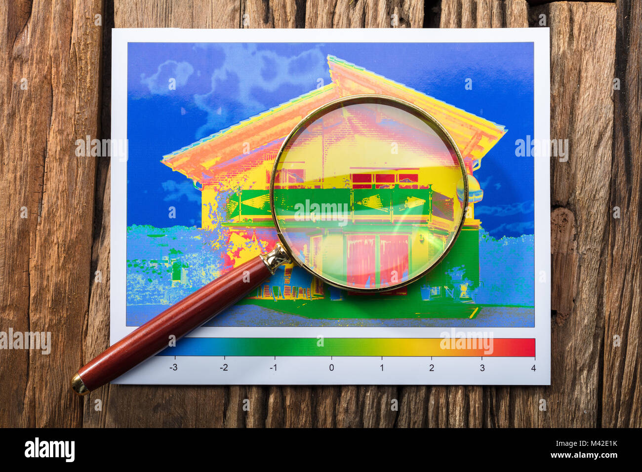Close-up Of Magnifying Glass On Heat Loss Efficiency Of A House Over Wooden Desk - Stock Image