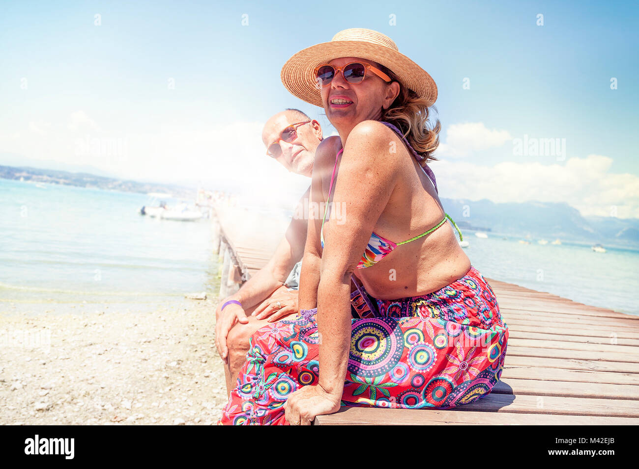 Portrait of modern mature couple relaxing in swimsuit sitting on the dock of a resort. Concept of beautiful people - Stock Image