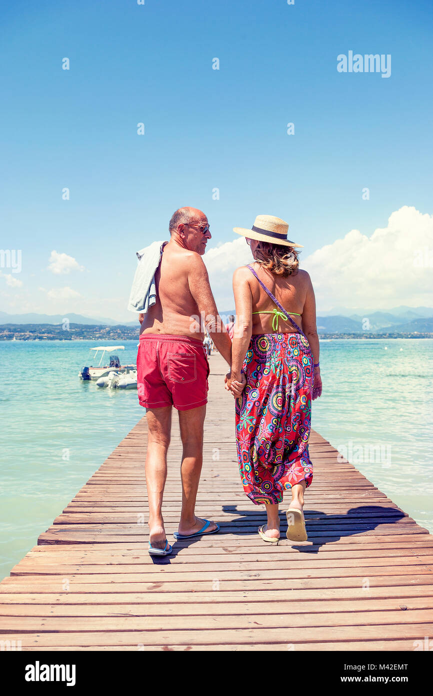 modern mature couple relaxing in swimsuit walking back on the dock of a resort. Concept of beautiful people having - Stock Image