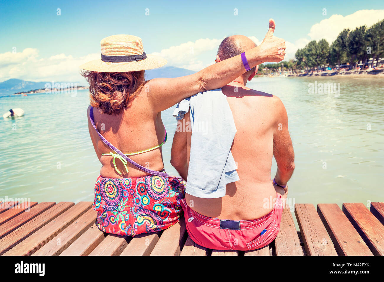 modern mature couple relaxing in swimsuit sitting back on the dock of a resort. Concept of beautiful people having - Stock Image