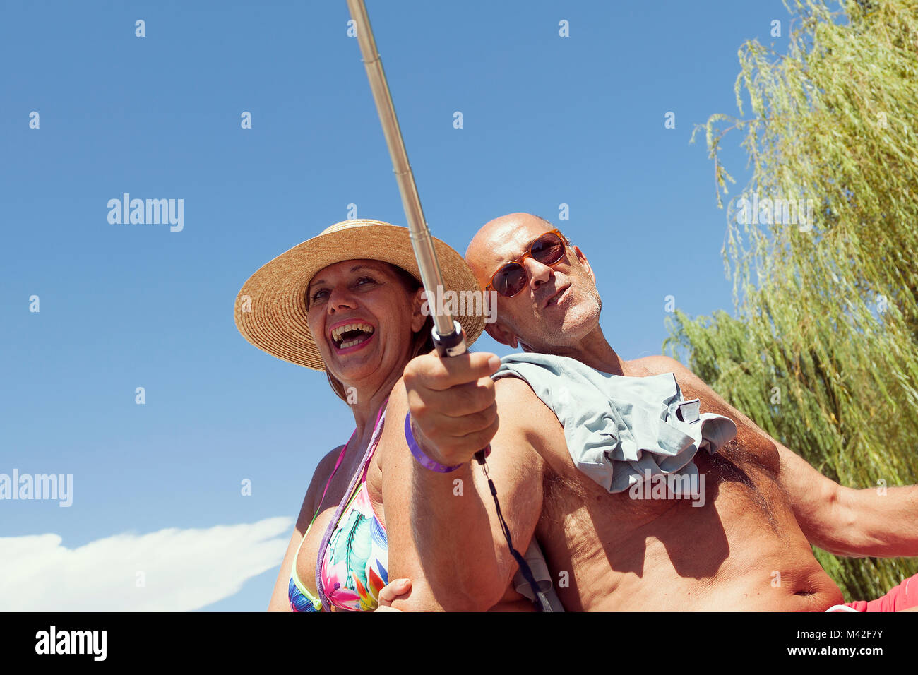 mature couple take a selfie with a smart phone on the beach on vacation. Concept of beautiful people having fun - Stock Image