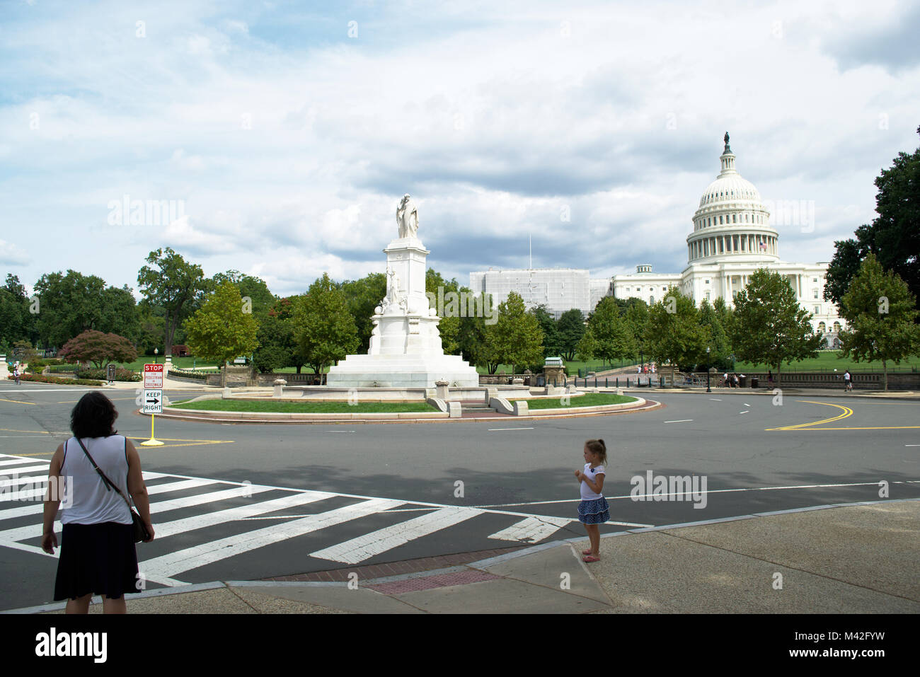 US Capital on the west side with cloudy skies and a woman and child crossing the street - Stock Image