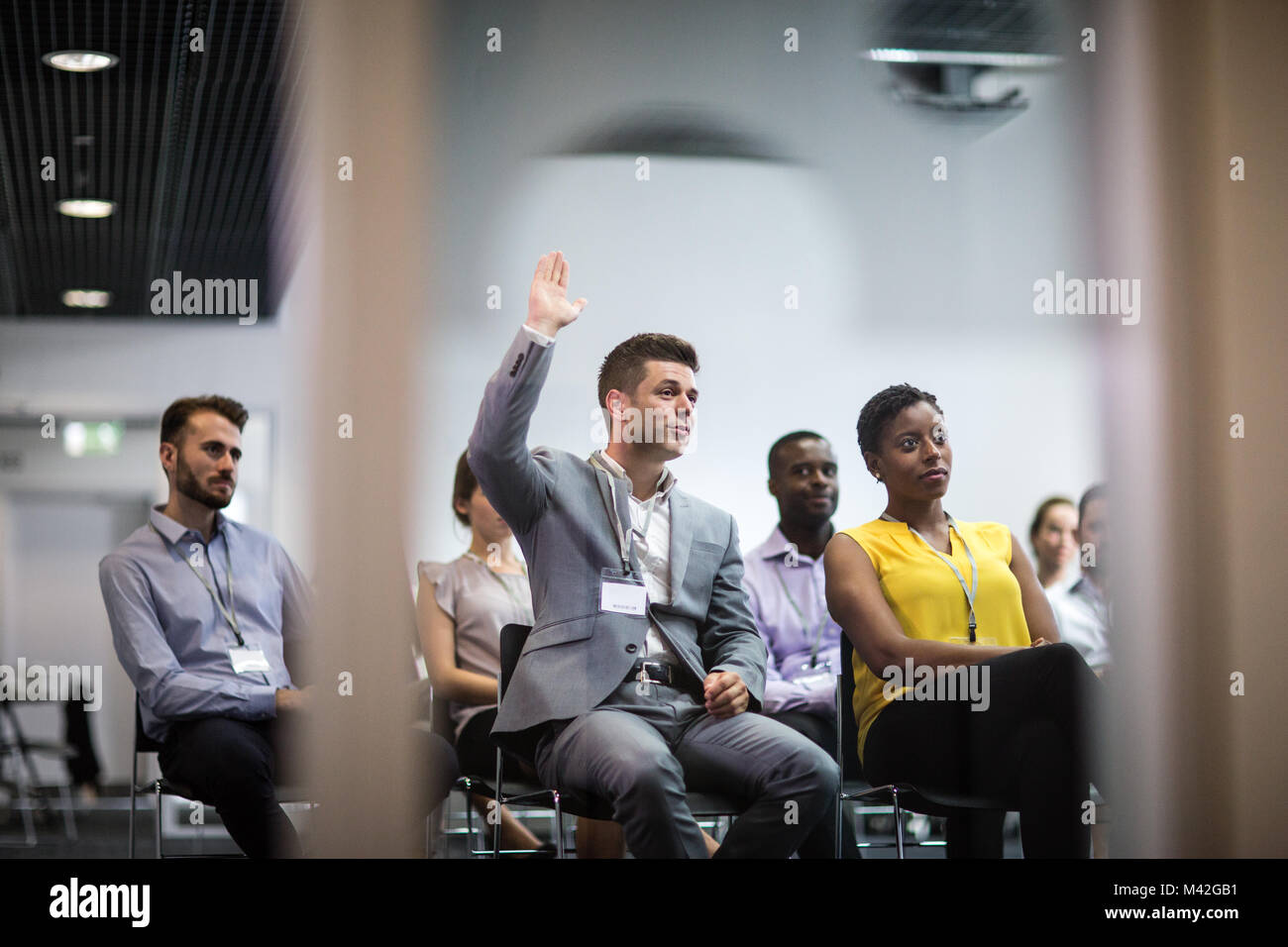 Businessman asking a question at a conference - Stock Image