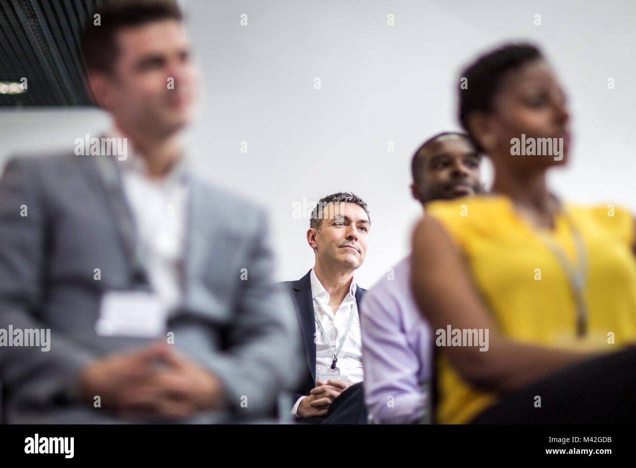 Businessman listening to a motivational speaker - Stock Image