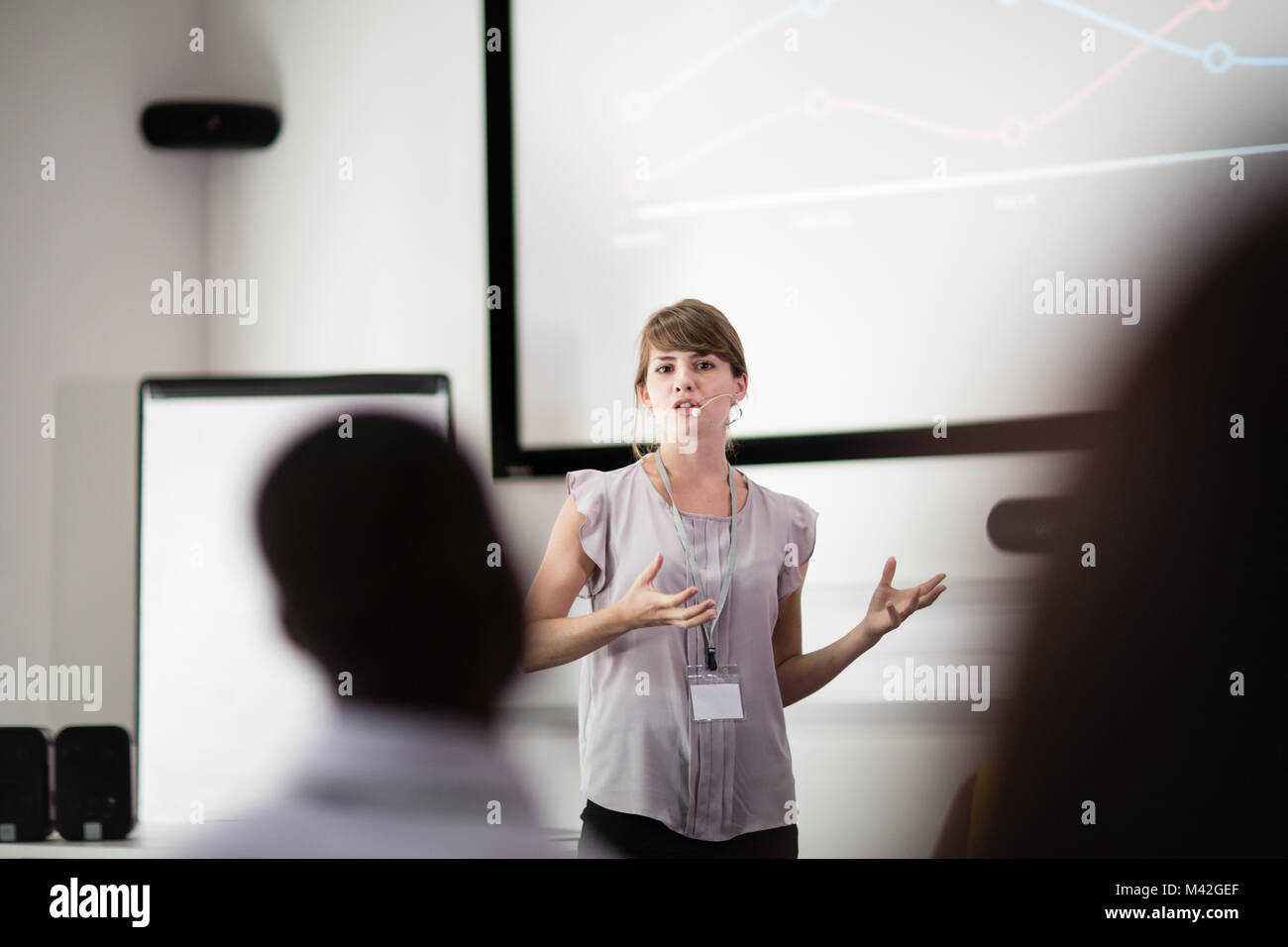 Young female executive speaking at a conference - Stock Image