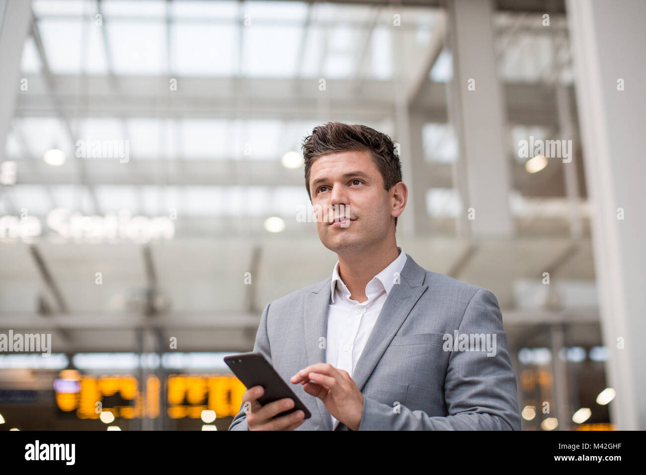 Commuter looking at train times at station holding smartphone - Stock Image