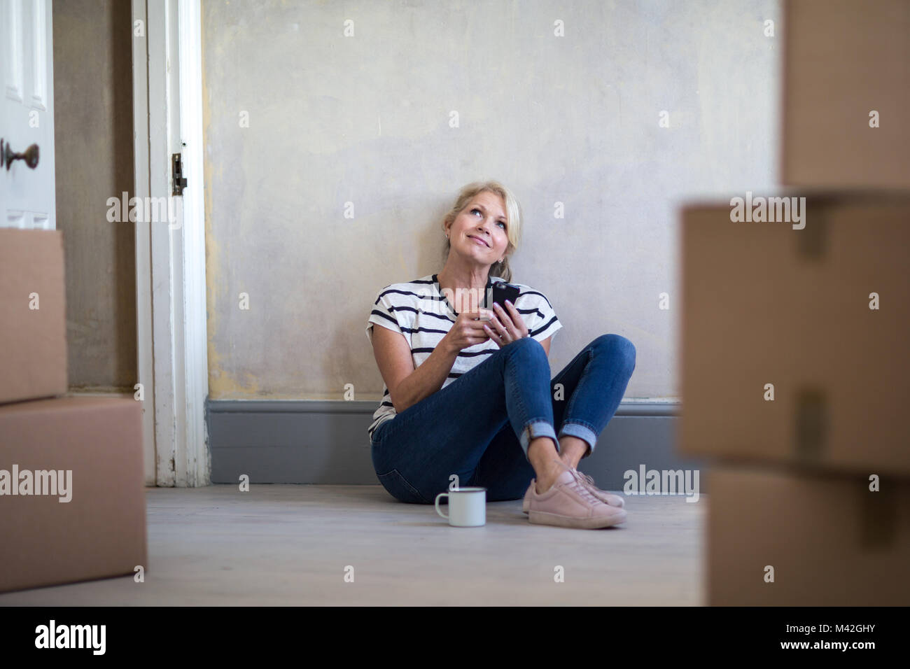Mature female sitting with moving boxes - Stock Image