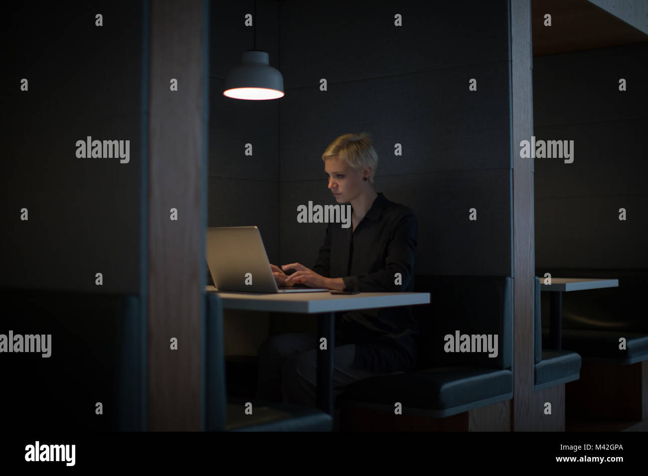 Businesswoman working late at night in office alone - Stock Image