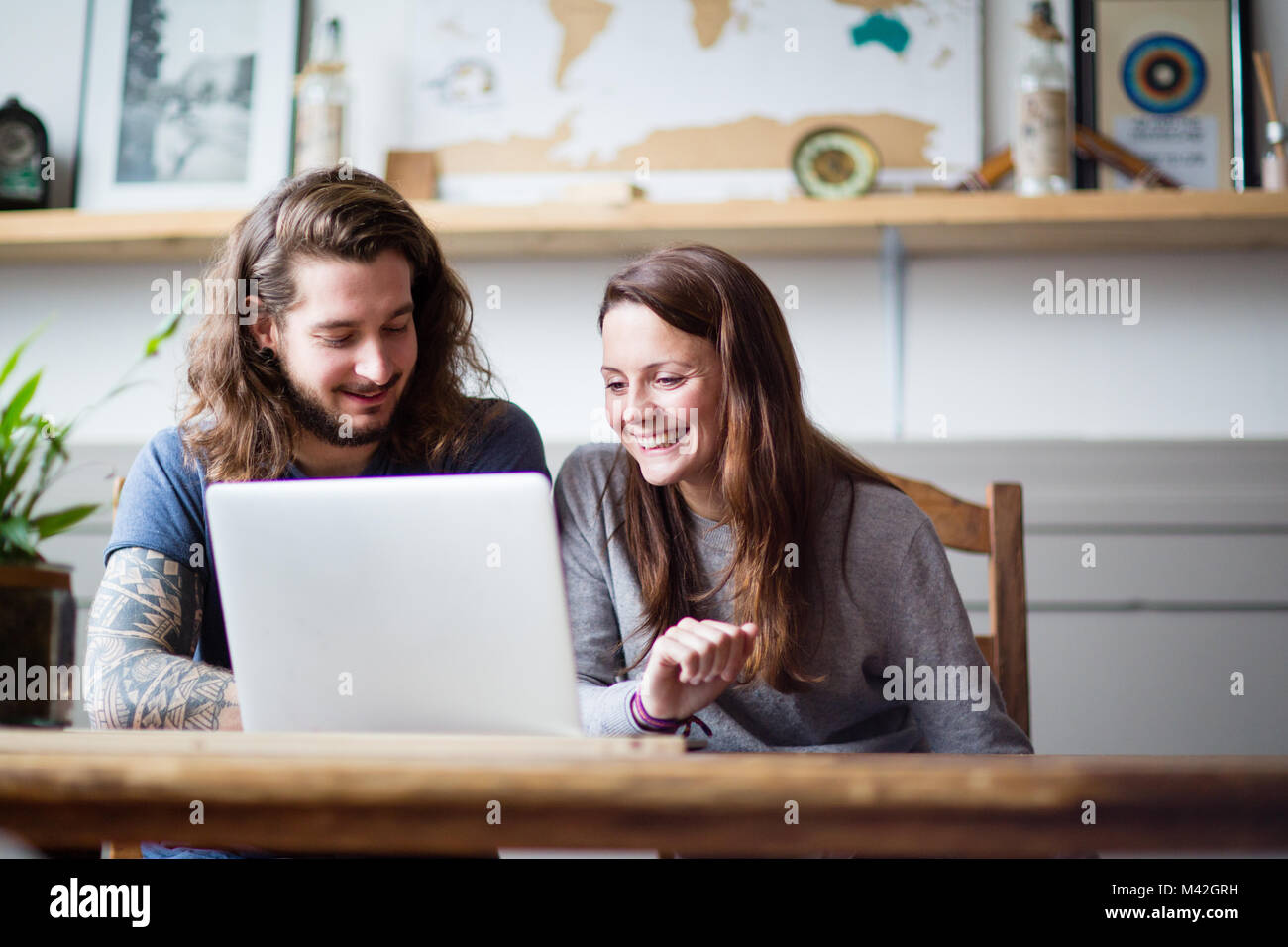 Young adult couple using a laptop together - Stock Image