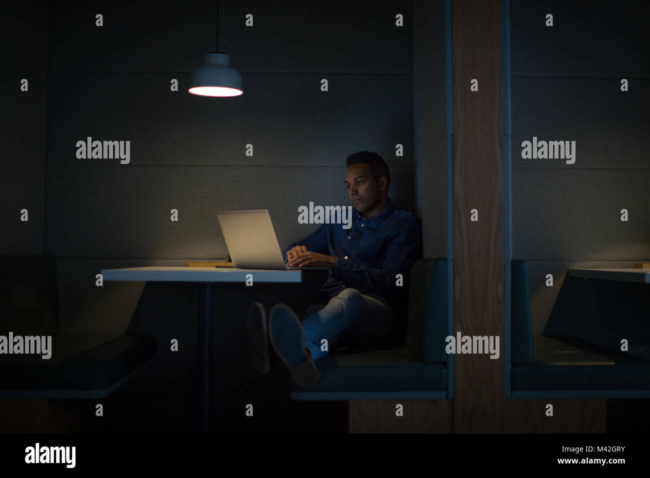 Businessman working late at night in office alone - Stock Image