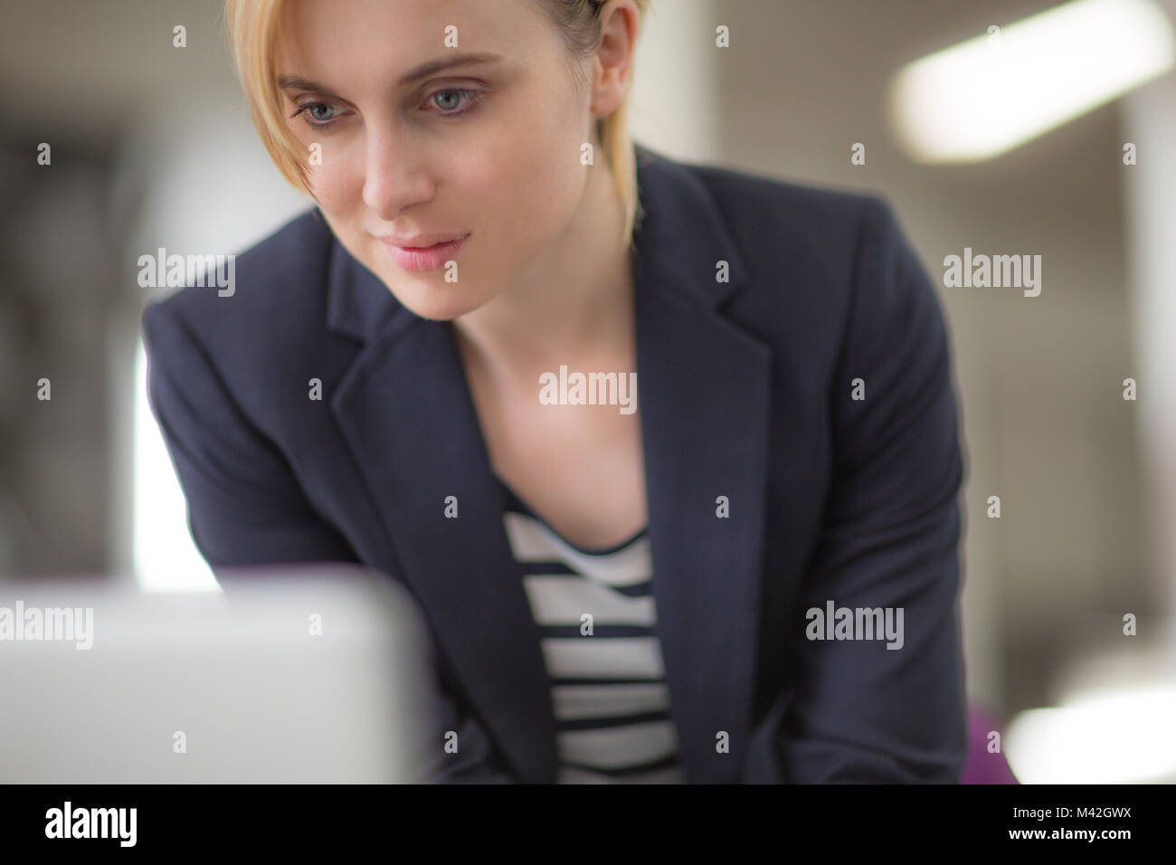 Young adult female looking at a laptop - Stock Image