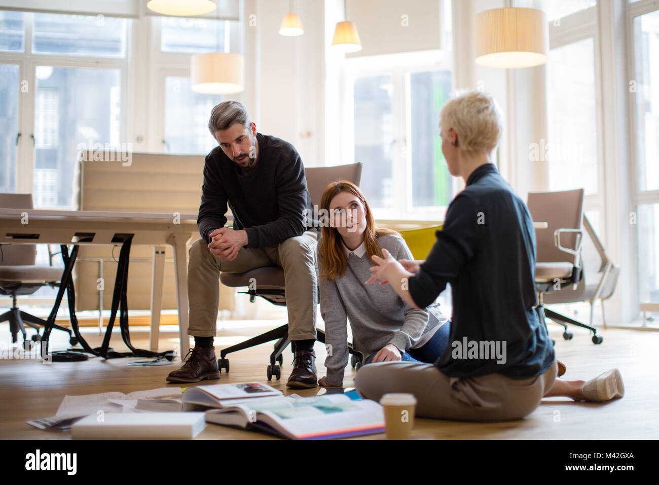 Group of designers discussing ideas with paperwork on office floor - Stock Image