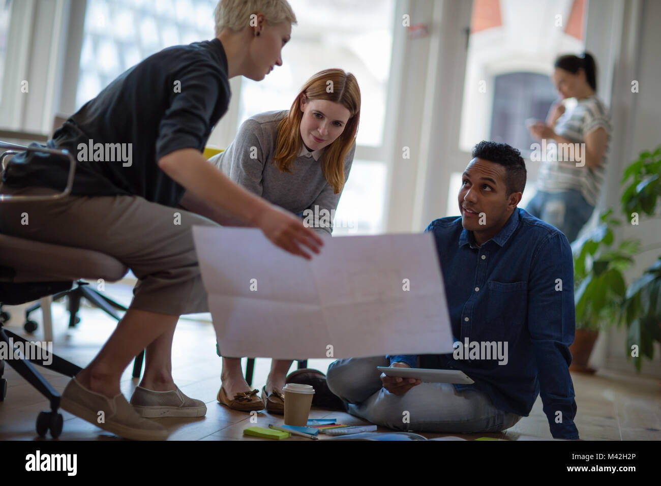 Colleagues looking at plans together in a meeting - Stock Image