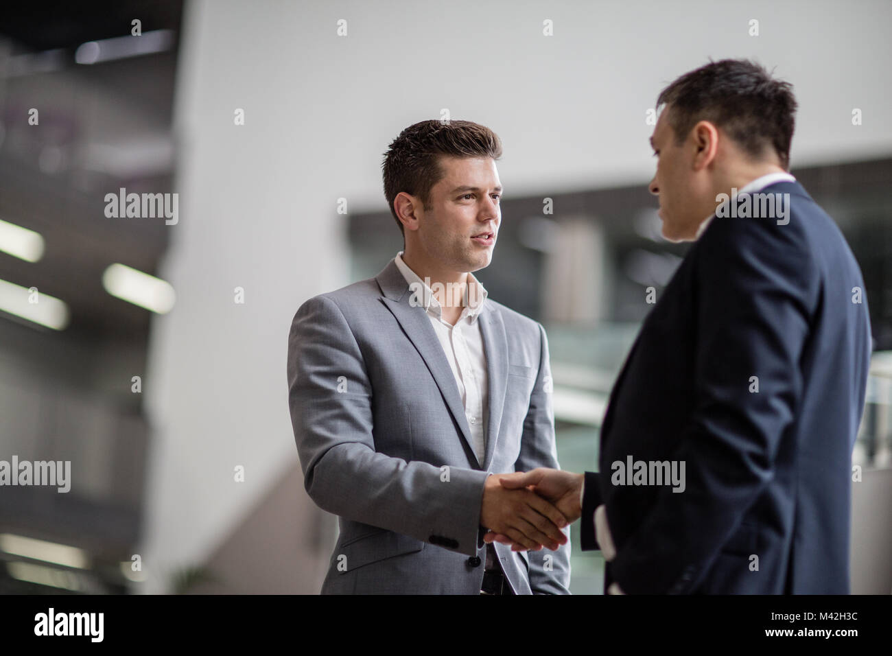 Businessmen shaking hands in a corporate office - Stock Image