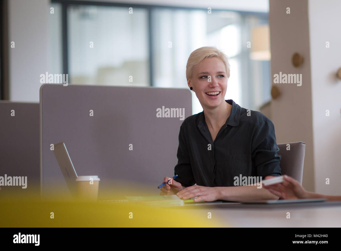 Businesswoman talking with colleague at work - Stock Image