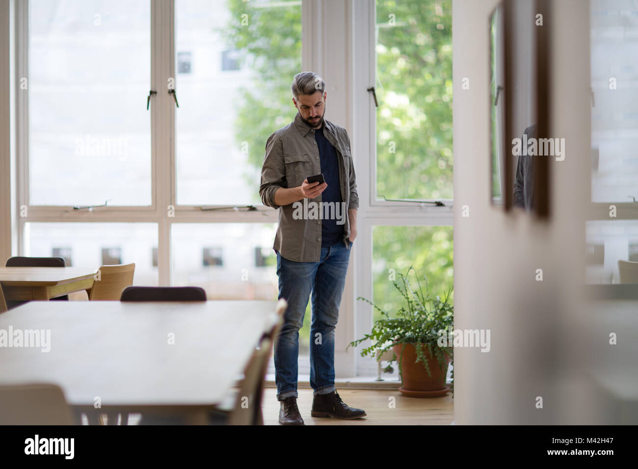 Businessman in empty office looking at smartphone - Stock Image