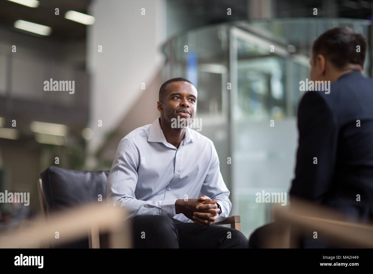 Businessman being asked a question in an interview - Stock Image