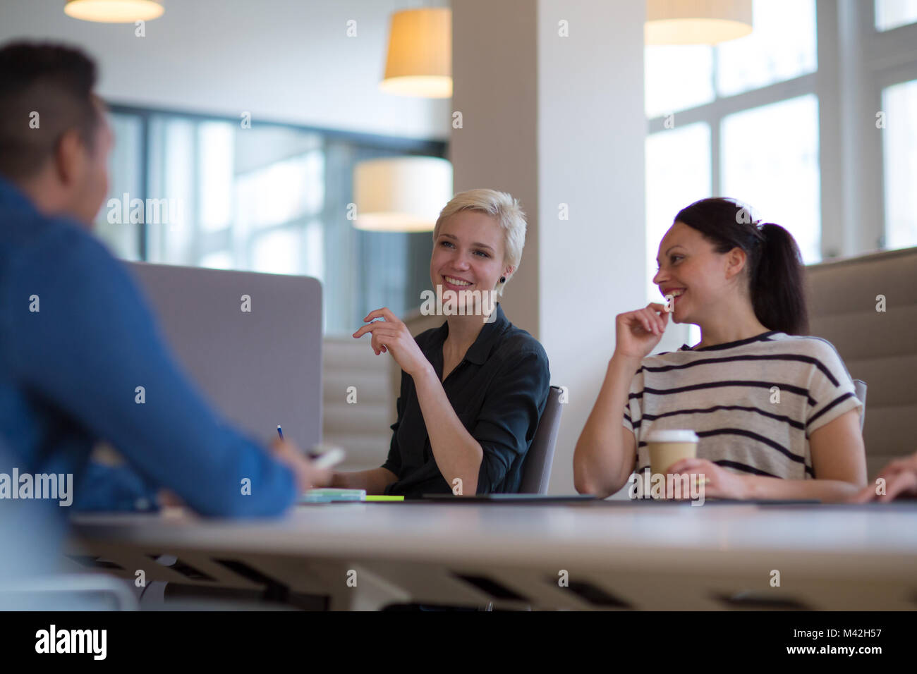 Business colleagues in a morning meeting with coffee - Stock Image