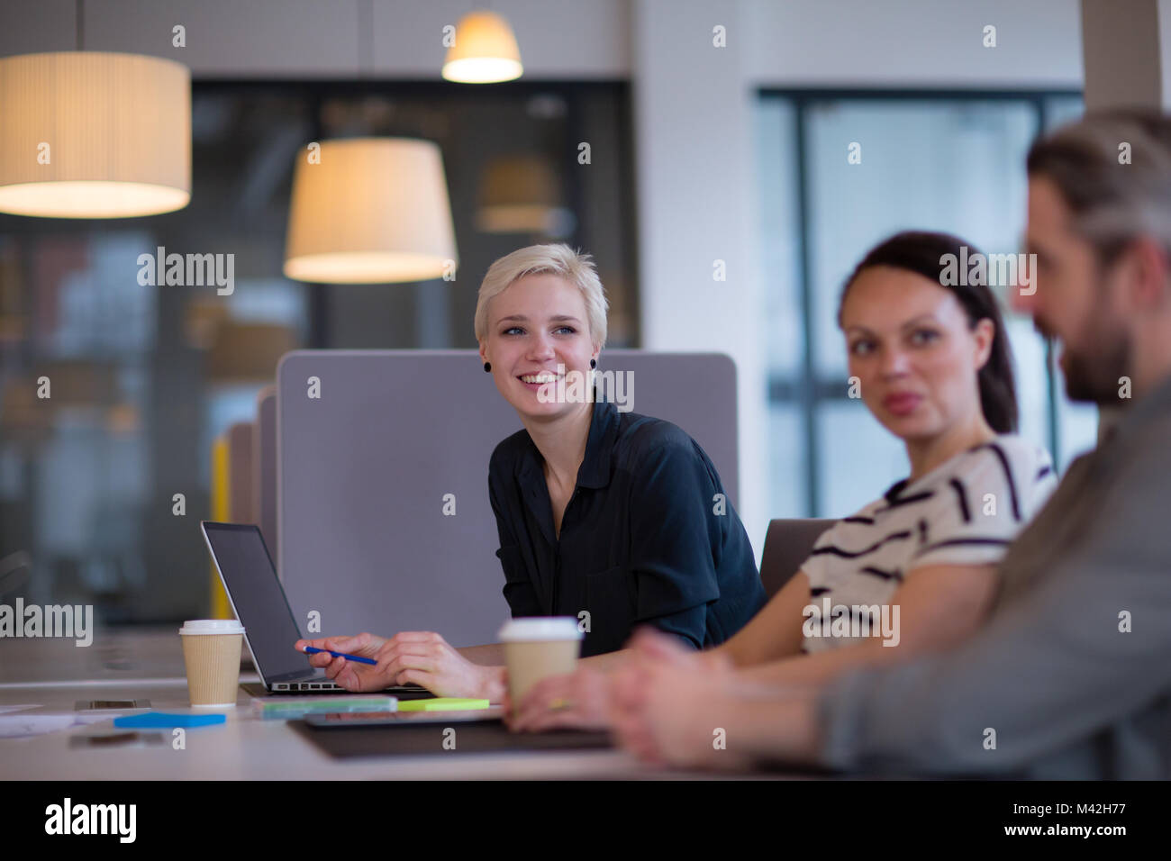 Business colleagues in a casual meeting with coffee - Stock Image