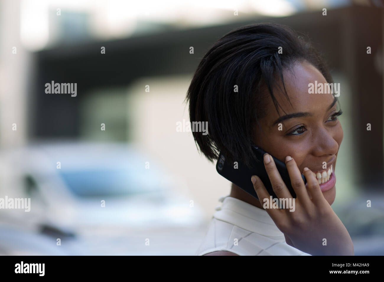 Businesswoman on way to work using smartphone - Stock Image