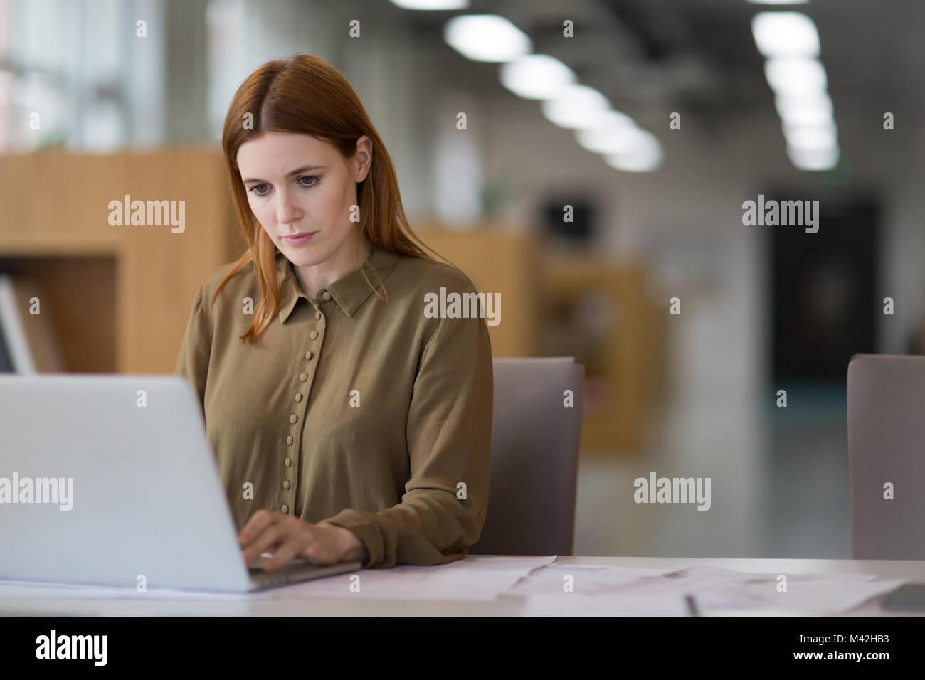 Female entrepreneur working on laptop - Stock Image
