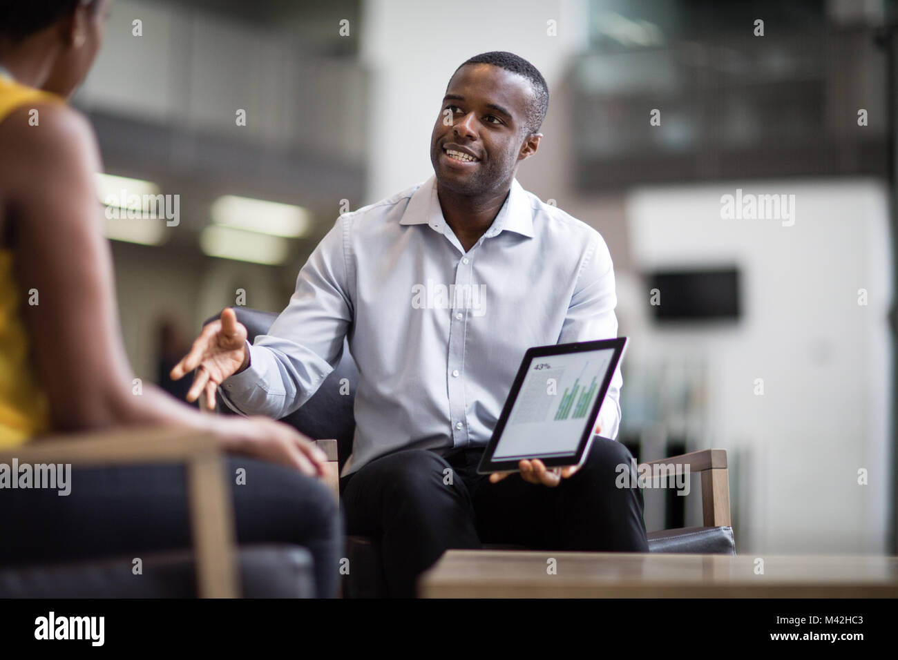 Business meeting in office atrium reception - Stock Image