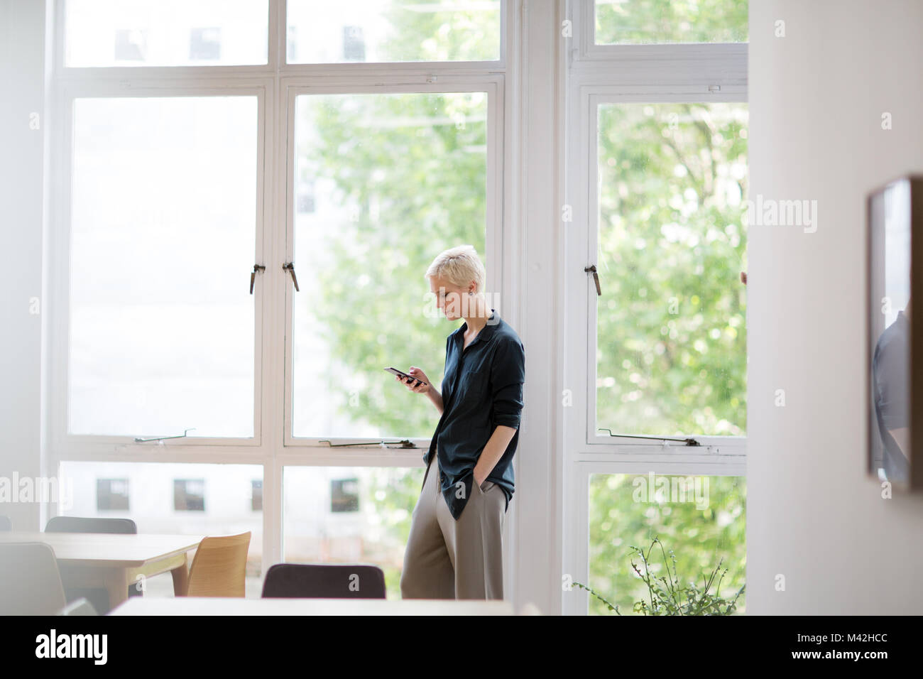 Businesswoman in empty office looking at smartphone - Stock Image