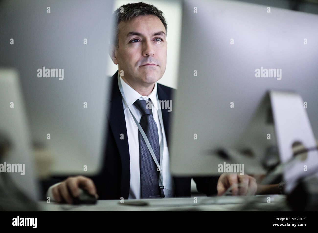 Businessman using computer late at night - Stock Image