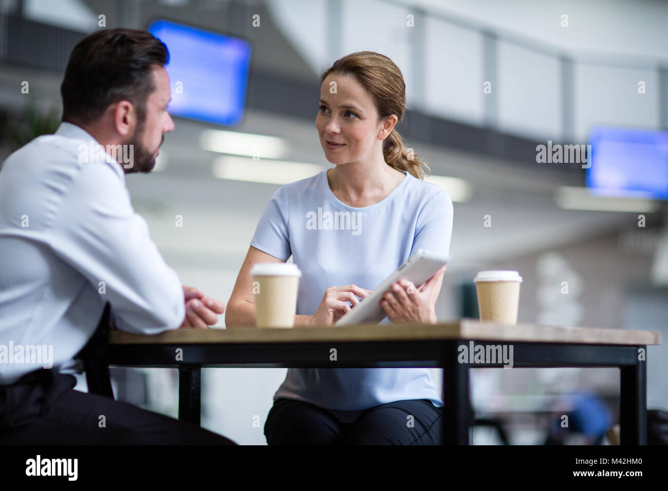 Businesswoman in a meeting using a digital tablet - Stock Image