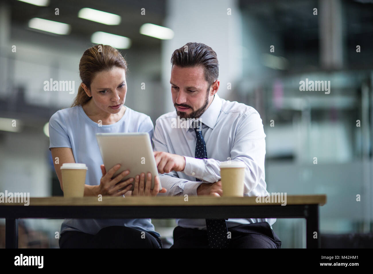Colleagues using a digital tablet in a meeting - Stock Image