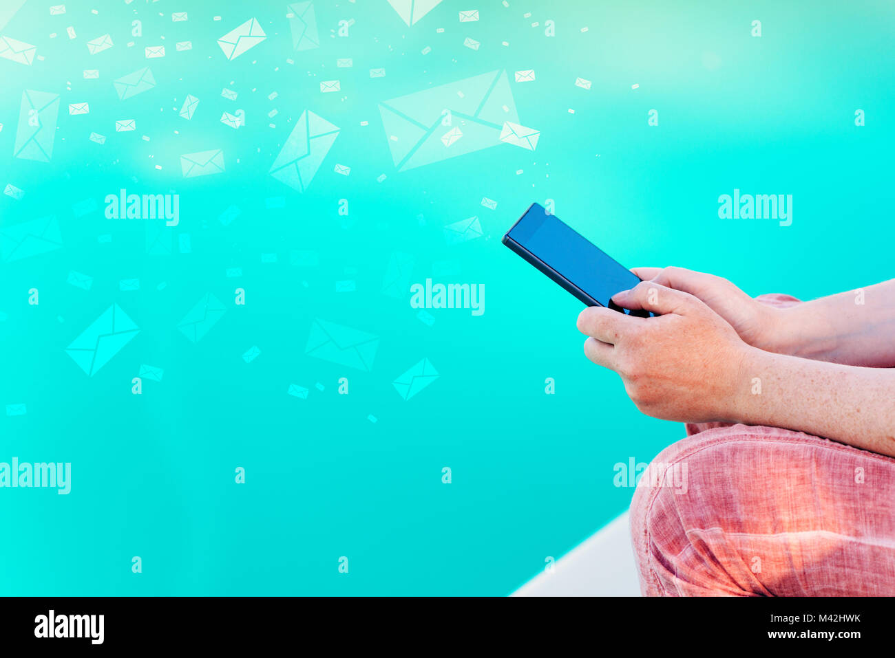Woman send bulk messages from her smartphone from summer vacation resort poolside - Stock Image