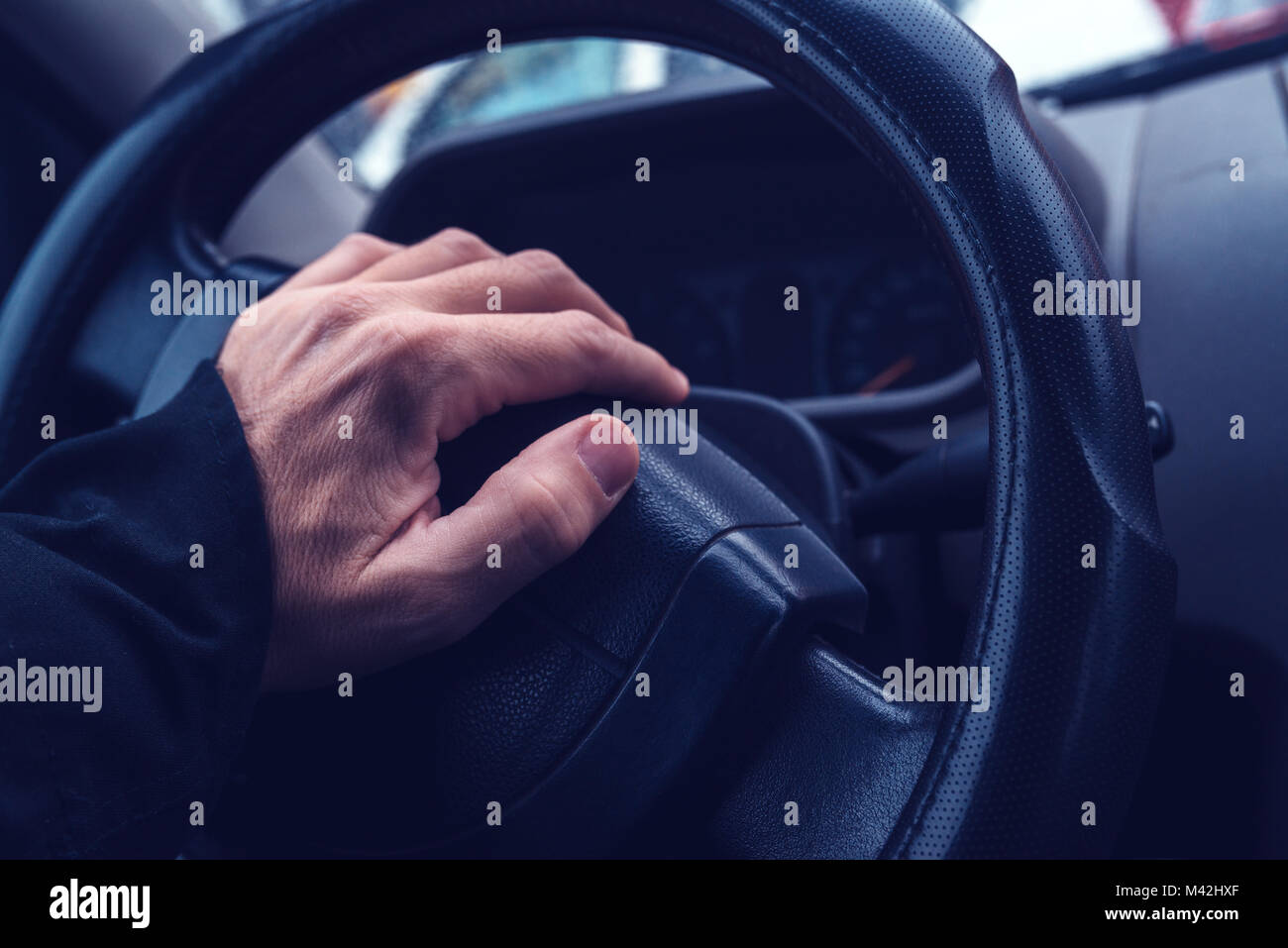 Male hand honking the car horn, man driving vehicle and beeping, ultra violey toned shadows - Stock Image
