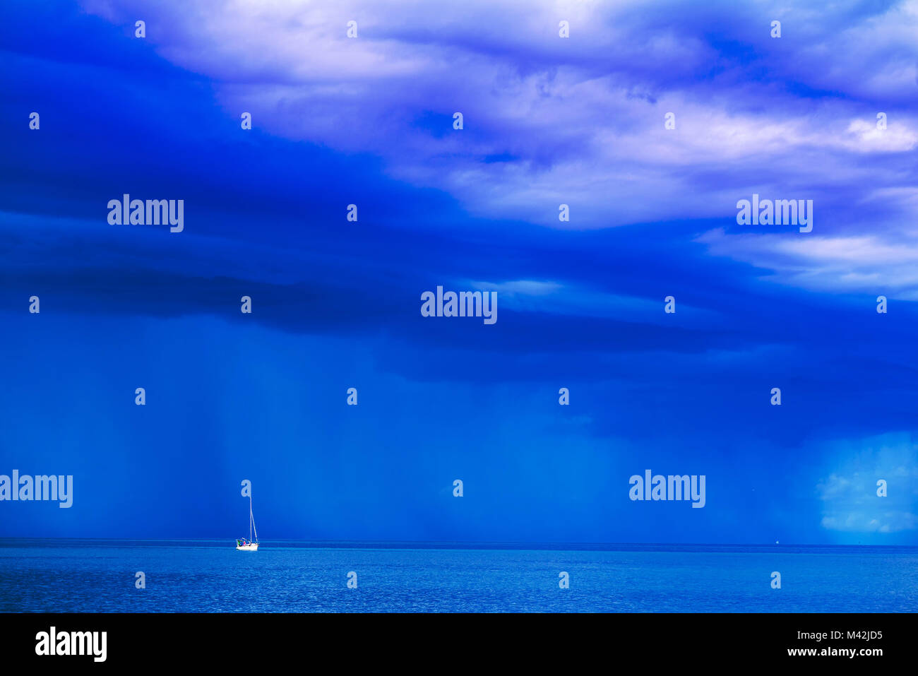 Sailing boat at stormy sea horizon with dark rainy clouds in background - Stock Image