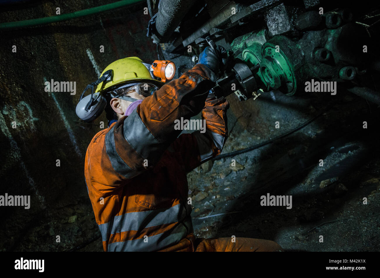 Miner fixing mineral extraction machine - Stock Image