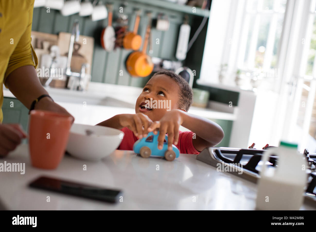 Boy playing at breakfast time - Stock Image