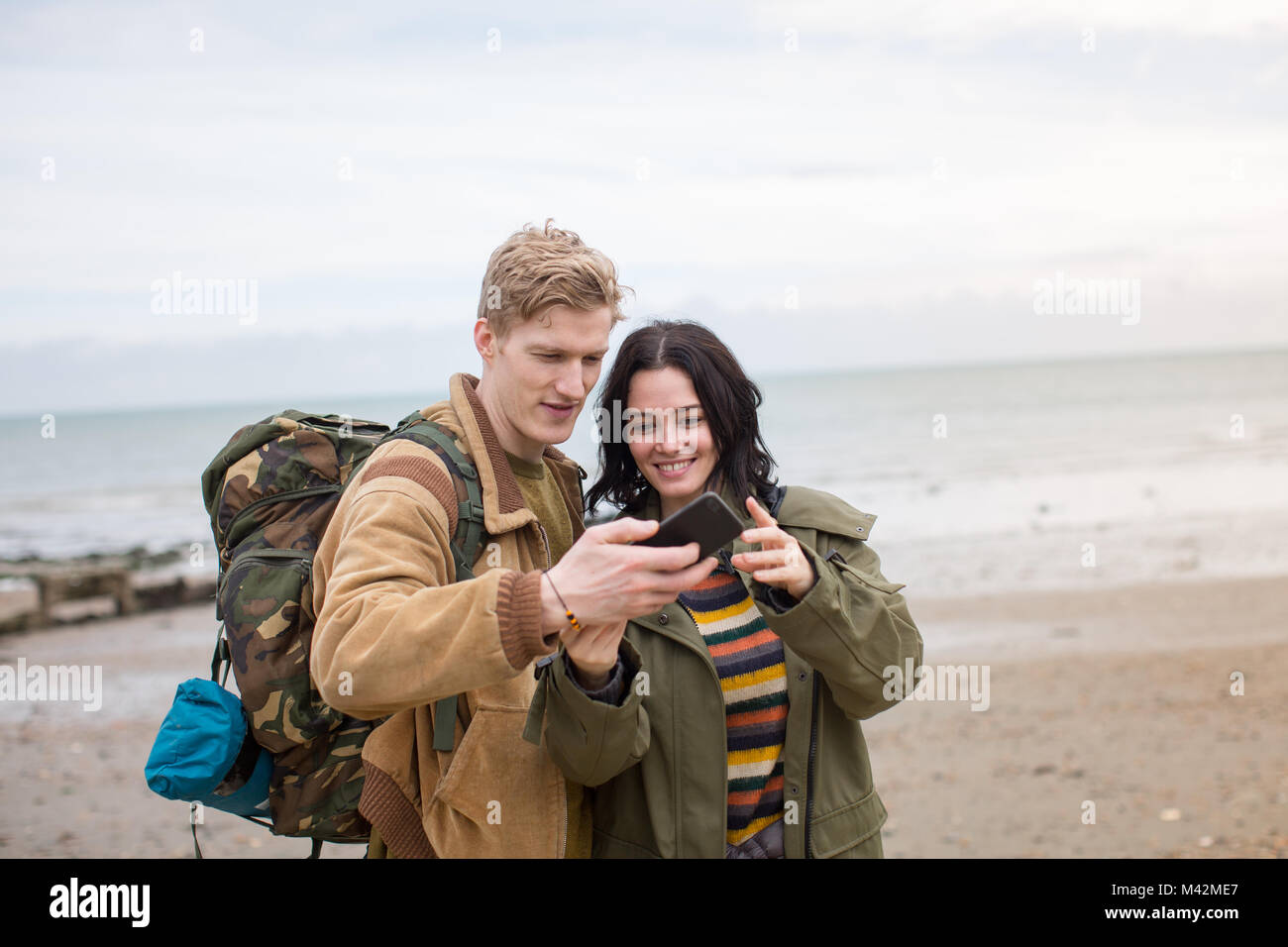Young couple using smartphone on a winter break at beach - Stock Image