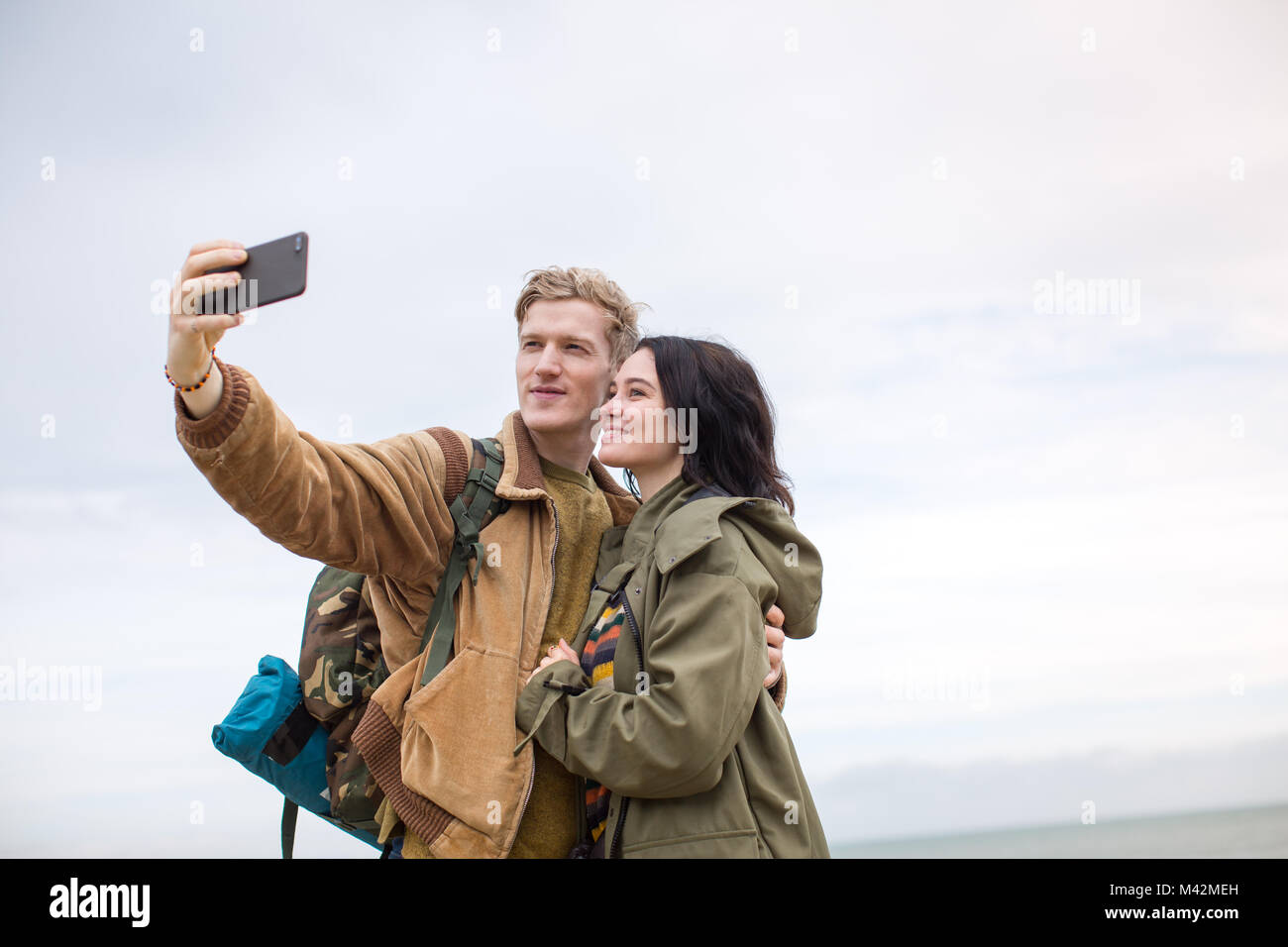 Young couple taking a selfie on a camping trip - Stock Image