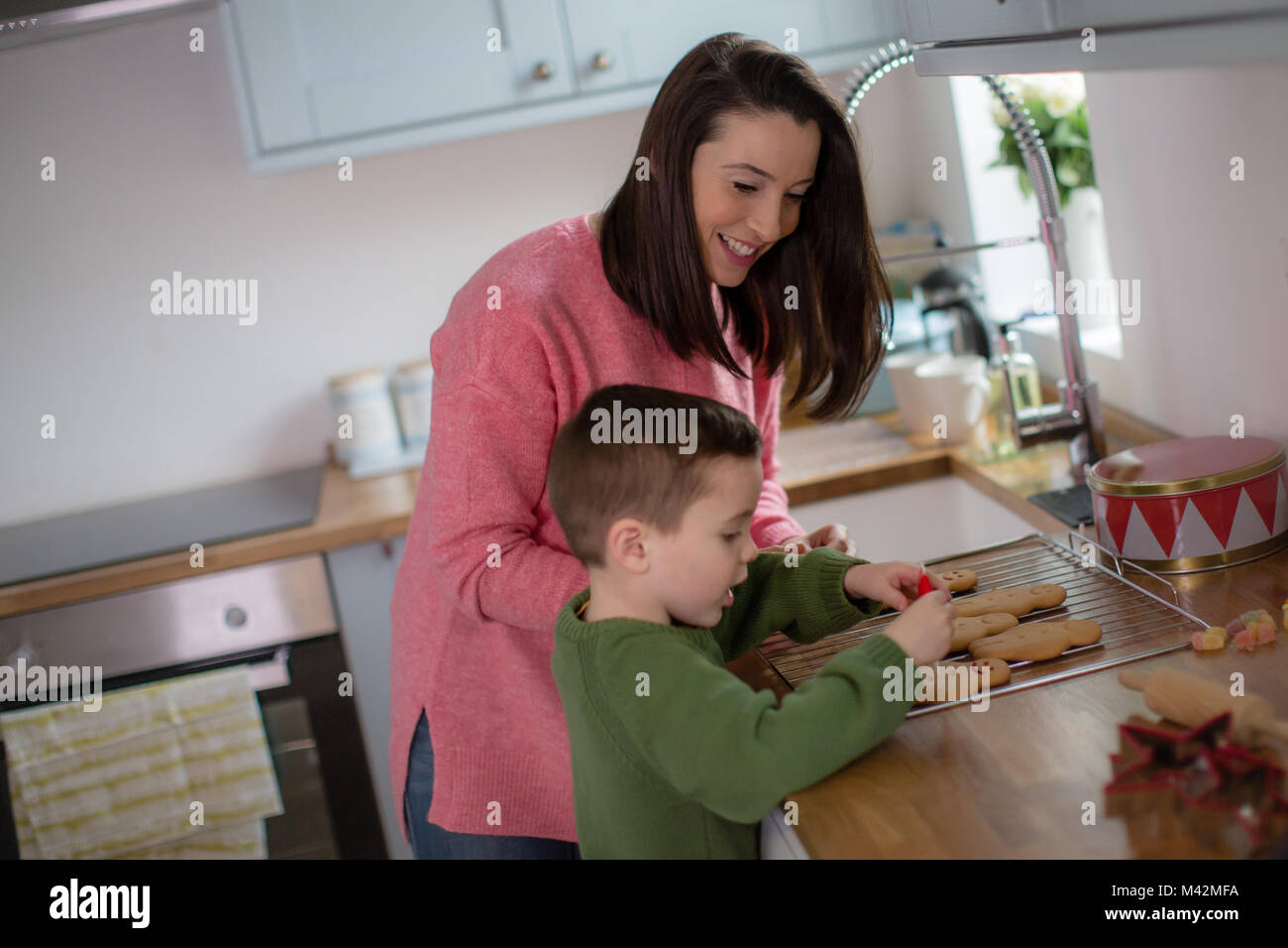 Mother and Son decorating gingerbread men - Stock Image