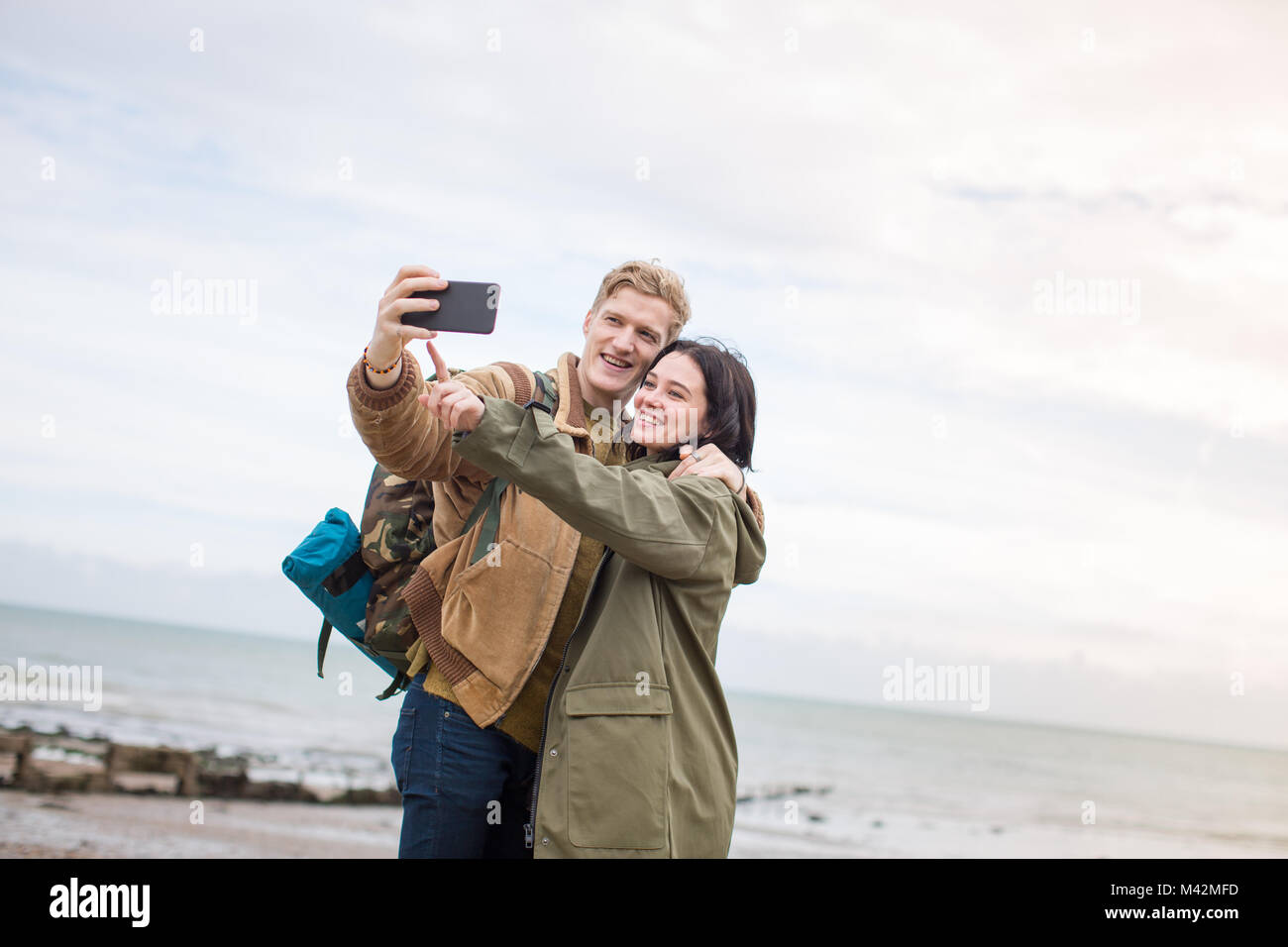 Young couple taking a selfie on the beach in winter - Stock Image