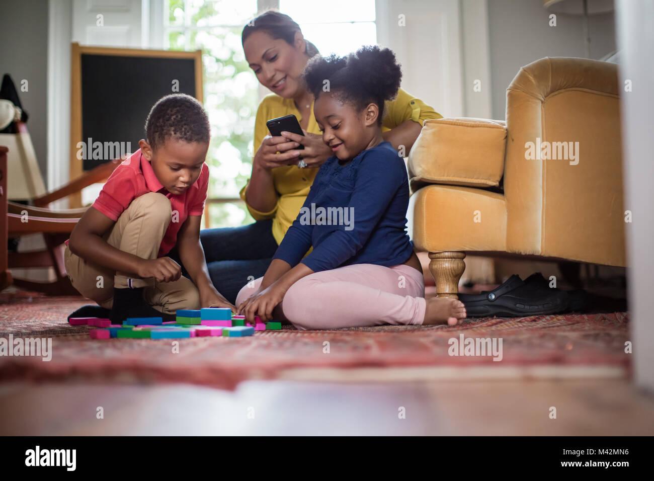 Mum using smartphone whilst children play - Stock Image