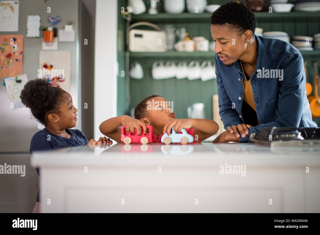 Brother and sister playing at breakfast time - Stock Image