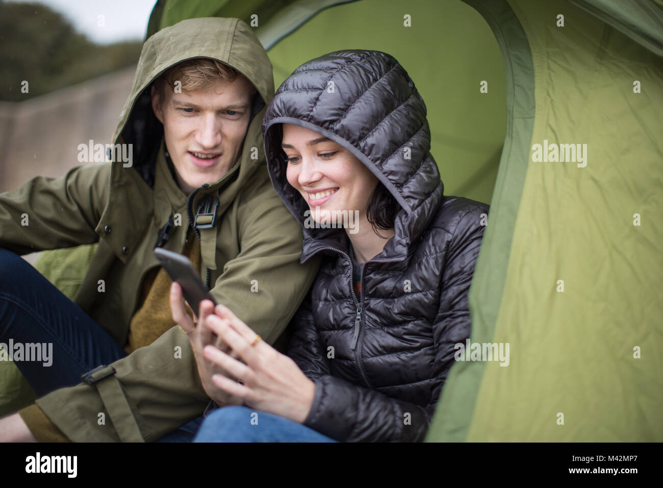 Young couple using a smartphone on a camping trip - Stock Image