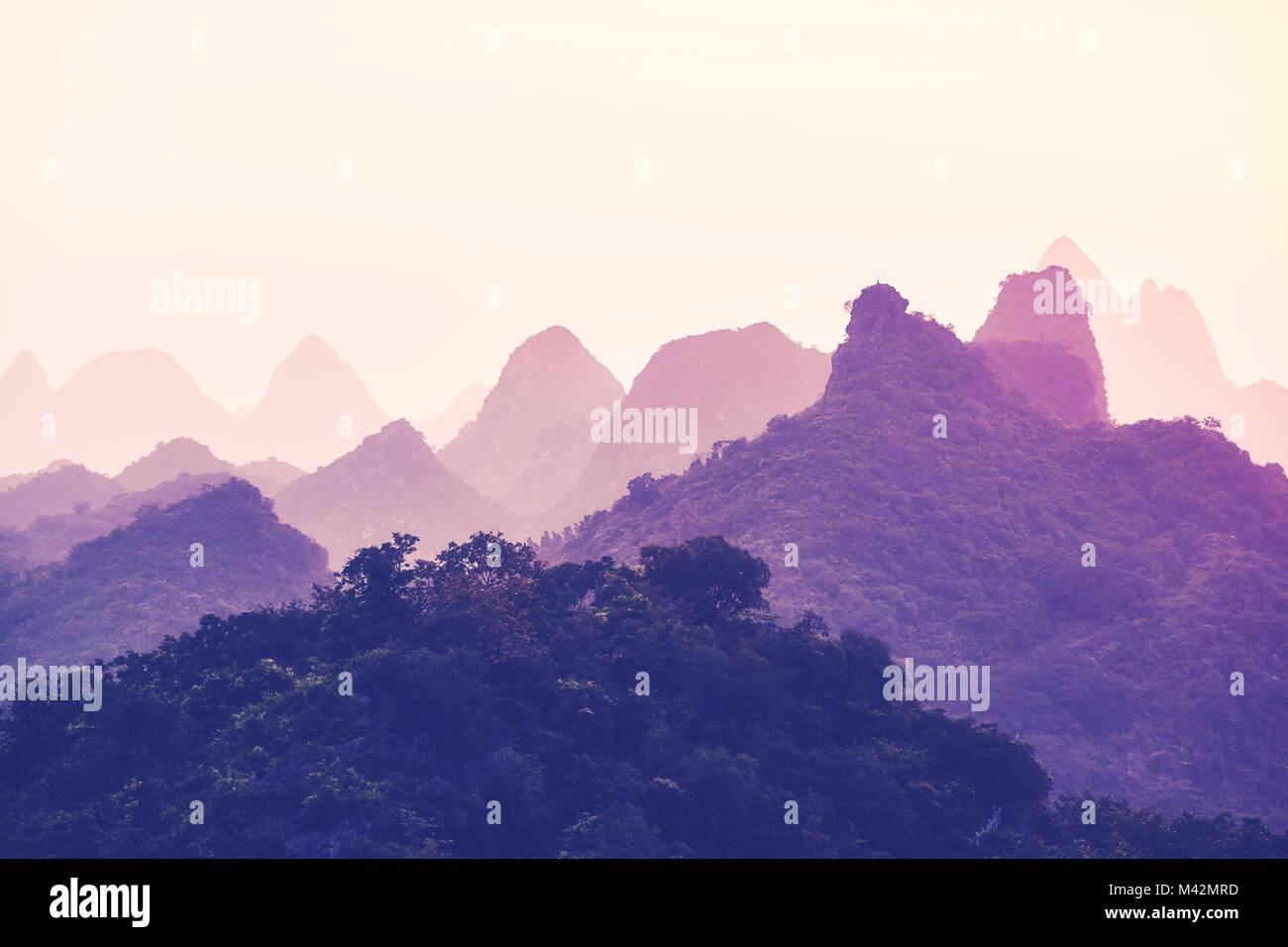 Scenic sunset over Karst mountains in Guilin, one of China top tourist destinations. Color toned picture. Stock Photo