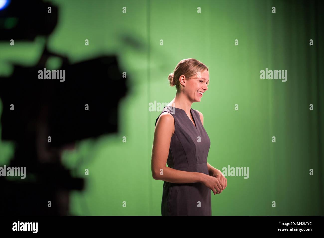 Presenter standing in a green screen studio - Stock Image