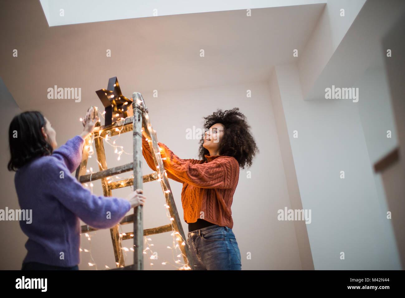 Friends decorating an alternative christmas tree - Stock Image