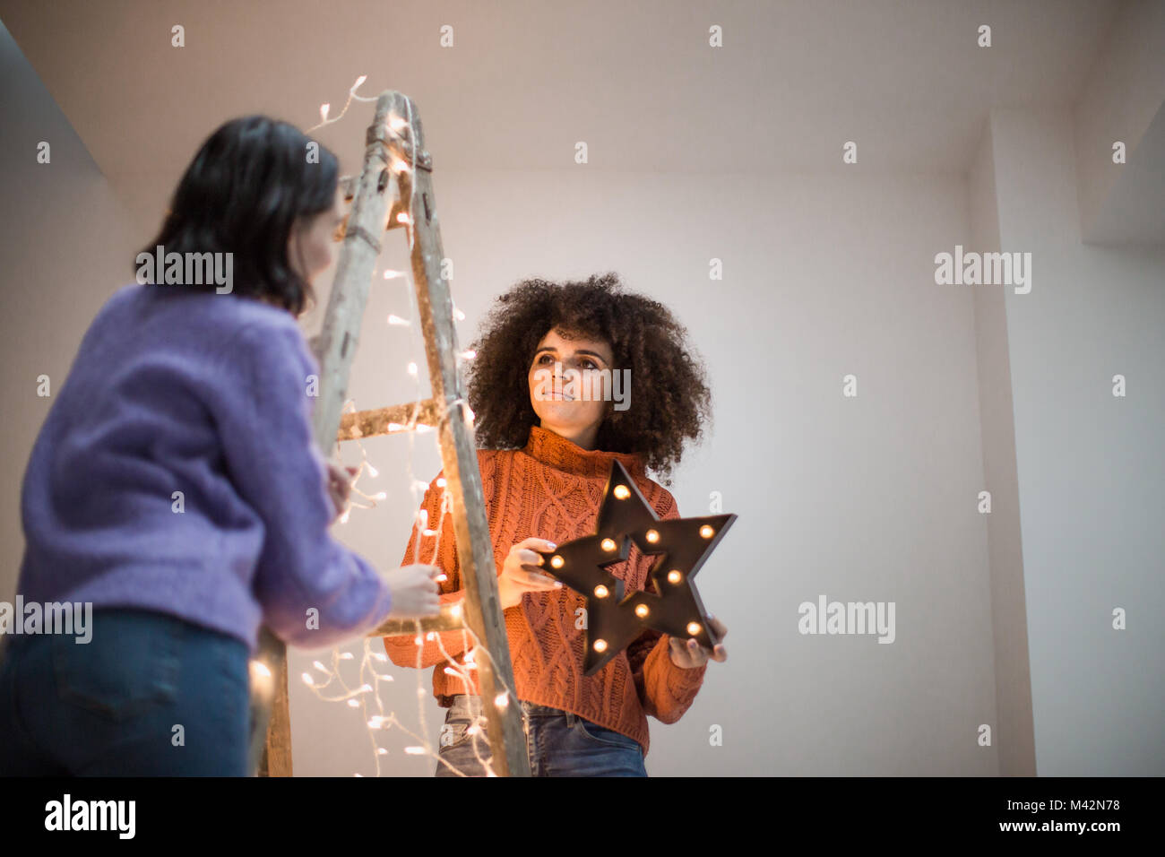 Friends decorating an alternative christmas tree - Stock Image