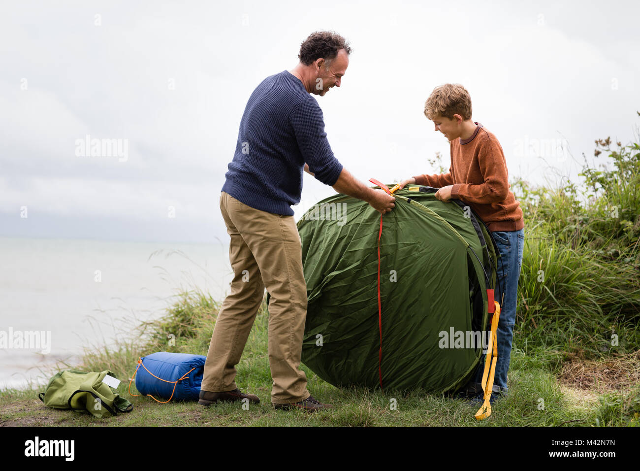 Father and Son putting up a tent together - Stock Image