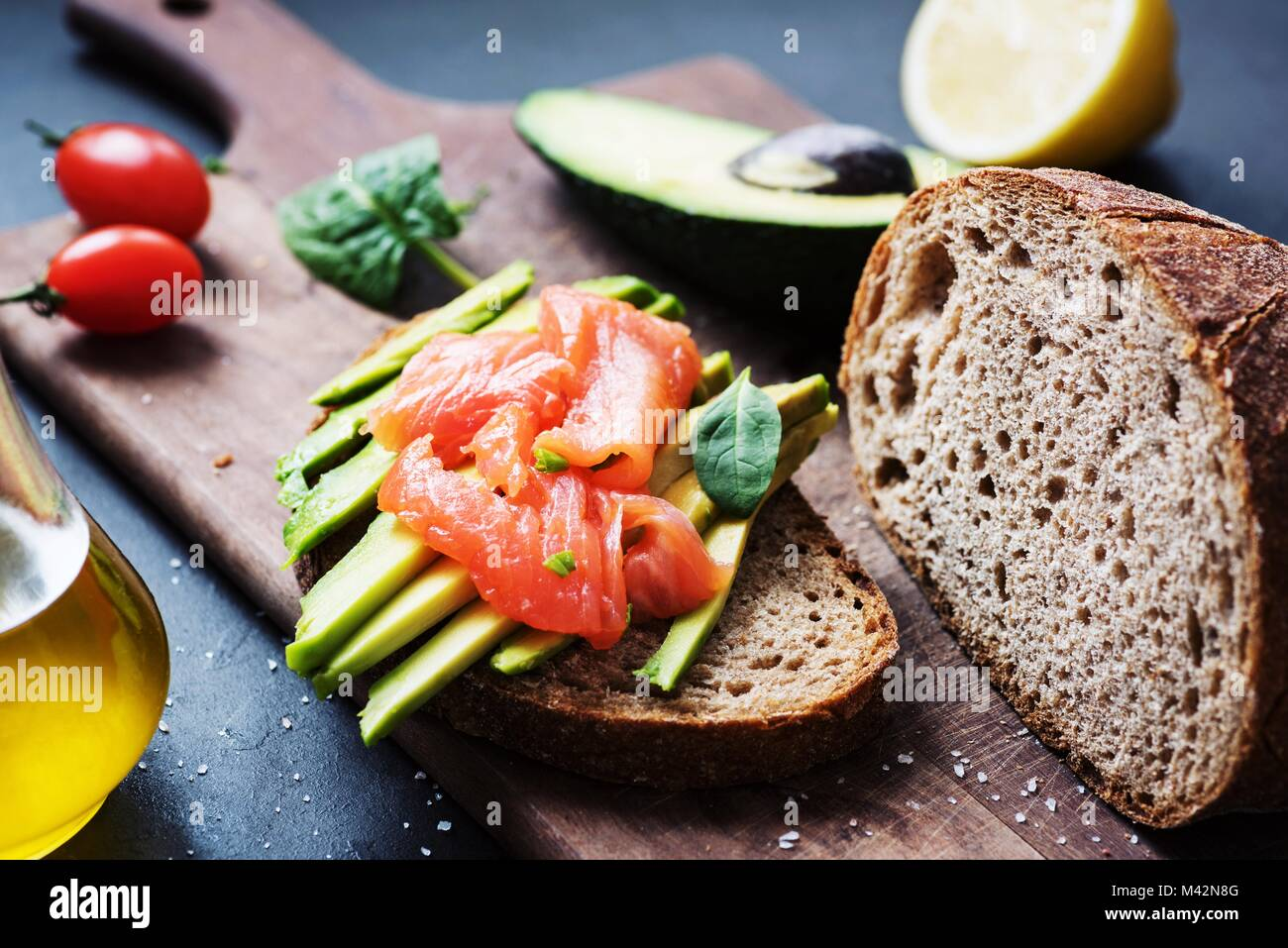 Rye toast with avocado and smoked salmon. Healthy snack - Stock Image