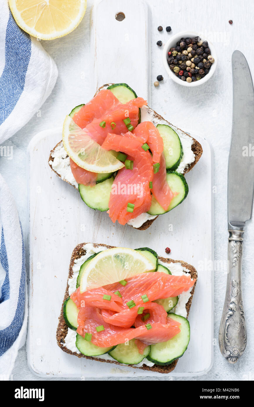 Smoked salmon, cream cheese and cucumber toast sandwiches on white. Top view - Stock Image
