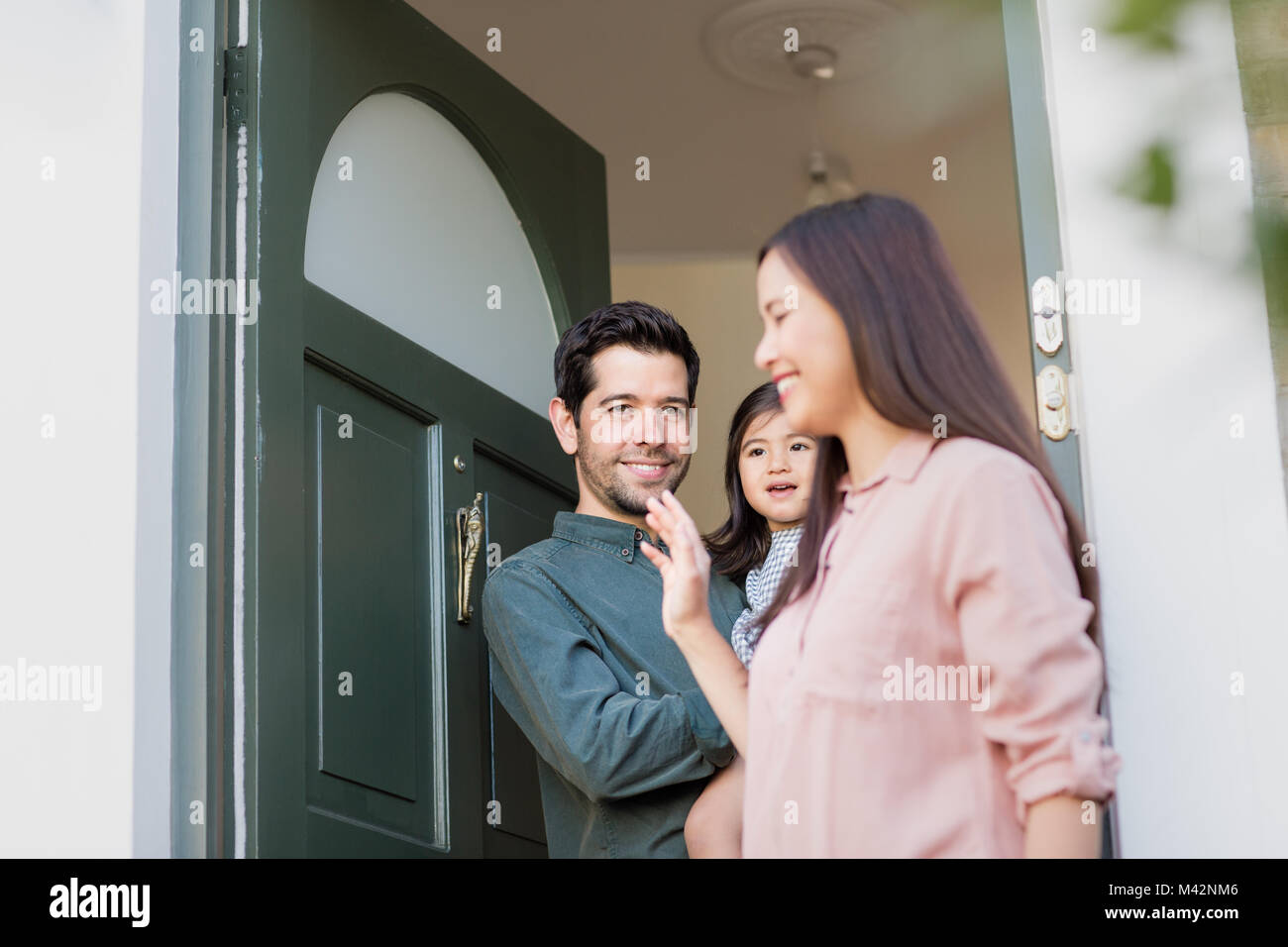 Father with Daughter waving goodbye to Mother - Stock Image